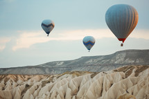 hot air balloons over desert canyon