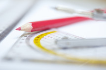 red colored pencil, protractor, and ruler