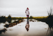 a girl in rainbows and a rain coat walking through a puddle