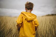 a boy in a rain coat walking through tall grass in a field