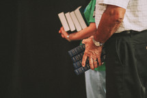 A man and woman with their hands full of Bibles.