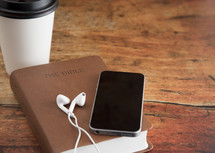 Bible and a Smart Phone with Earphones on a Wood Table