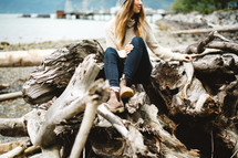 a woman sitting on a pile of driftwood