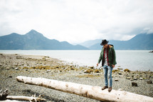a man balancing on a log on a shore