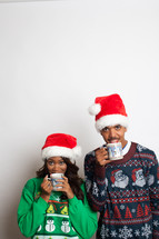 couple in ugly Christmas sweaters and santa hats sipping hot cocoa