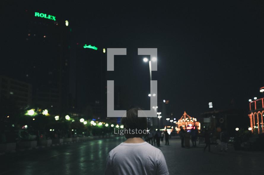 pedestrians walking on a city sidewalk at night