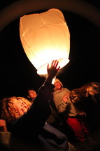 friends lighting a floating paper lantern at night