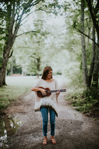 a teen girl standing on a dirt road playing a ukulele