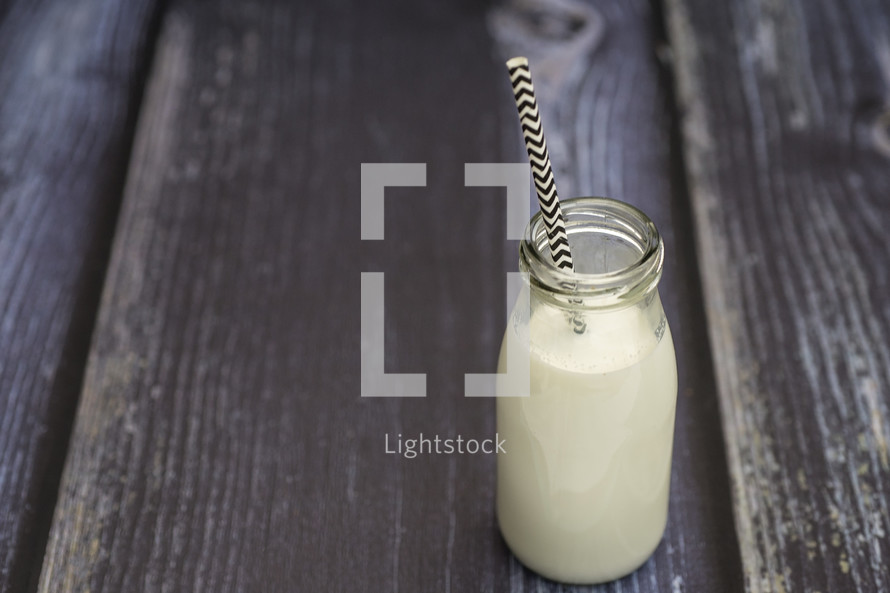 milk in a glass bottle with a straw