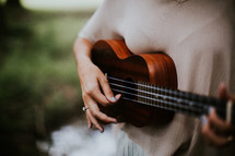 a woman playing a ukulele