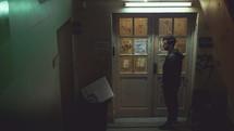 a man standing in front of a doorway in a dark hallway