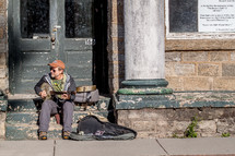 Man playing a banjo on the steps of an abandoned building.