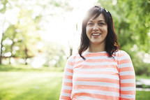 smiling woman standing in a yard.