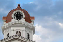 Clock on the domed tower of a church.