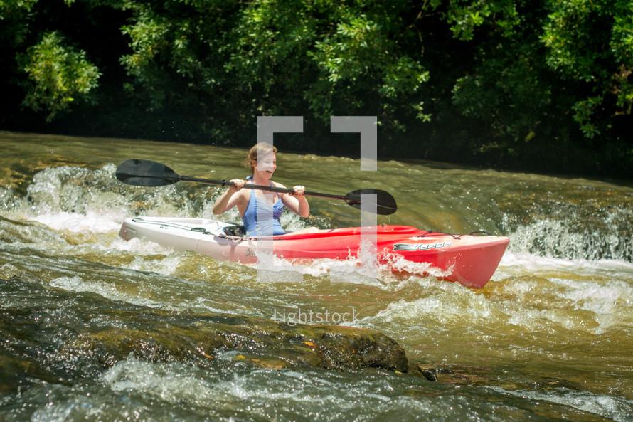 woman kayaking in rapids