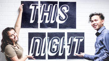 teens pointing to a poster that reads This Night