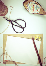 twine, scissors, letter, envelope, brown paper, stamps, pen