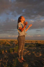 a teen girl with raised hands standing in a field