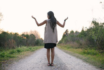 young woman standing on a gravel road with hands raised