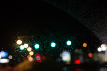 water droplets on a windshield and bokeh taillights