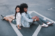 two young women sitting in a parking lot
