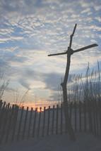 a cross of sticks on sand dunes