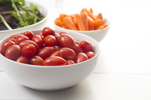 bowl of cherry tomatoes, carrots, and leafy greens