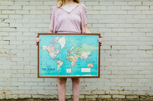 woman holding a framed world map
