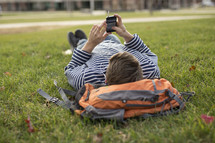 a college student lying in the grass listening to a podcast