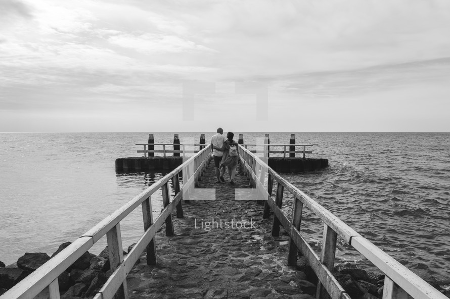 couple walking on a pier