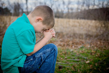 boy child with head bowed in prayer