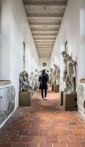 a woman admiring statues in a museum