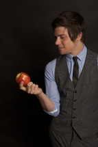 man in a vest and tie holding an apple