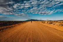man standing in the middle of a dirt road
