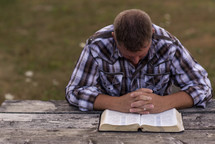 a man praying over the pages of a Bible outdoors