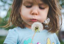 a child blowing a dandelion