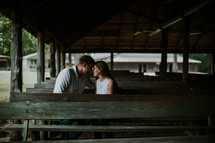 couple sitting in wooden pews outdoors - couple's retreat