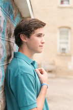 young man in a polo shirt leaning against a graffiti covered wall