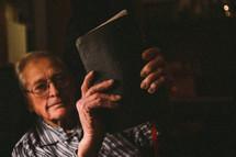 An older man holding a Bible.