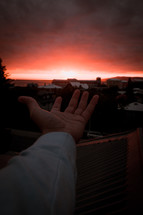 a hand reaching out towards a red sky at sunset