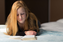 a teen girl reading a Bible on a bed