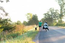 women walking down a country road walking a dog