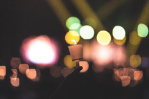 bokeh lights and raised hands holding candles