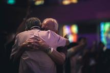 elderly men hugging at a worship service