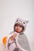 a girl toddler in a Halloween costume with a sucker