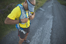 A runner putting on a hydration vest.