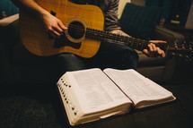 A man sitting on the couch playing his guitar in front of an open Bible.