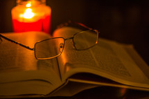 reading glasses on the pages of a Bible and a candle