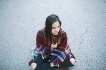a lost teen wrapped in a blanket sitting on asphalt