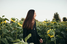 a woman standing in a field of sunflowers